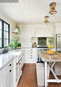 White Coastal Farmhouse Kitchen: Wood Floor, Range Hood, Industrial Style Nautical Lighting