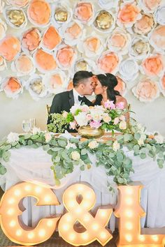 modern sweet table with paper flower backdrop and marquee monogram