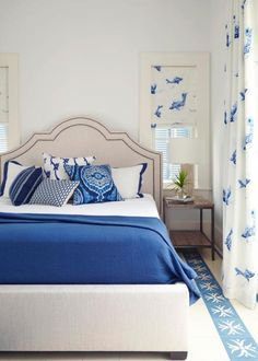 Blue and white make for a crisp, ocean-inspired color palette in this beautiful bedroom. A fun fish print for the shade and curtains furthers evokes the seaside setting.