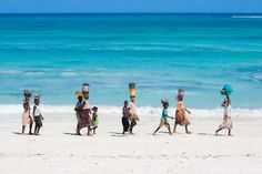 Africa |  People.  A group of Makua women and children carrying their catch of the day in front of the turquoise water of the Indian Ocean as they go back home.   Pemba (Mozambique)