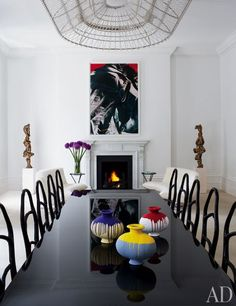 A Fredrikson Stallard light fixture hangs over the first-floor dining table, which is topped with a trio of Ai Weiwei vases and lined with Bonetti chairs.