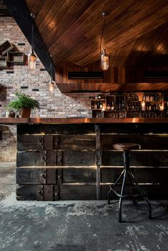 Reclaimed timber boards and sections of mesh fencing feature in this dimly-lit bar in Sydney