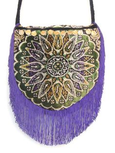 This Bohemian bags flap is made from a vintage velvet with a mandala design. The gypsy bag has 6 inch purple fringe around the flap which