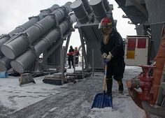 Sonar Technician (Surface) 3rd Class Princess Sonores shovels snow off the deck of the Arleigh Burke-class guided-missile destroyer USS Benfold (DDG 65).
