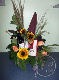 Bring in a wine bottle and we can make a gorgeous gift basket with chocolates and the flowers of your choice! Featured here are local sunflowers and seed grasses.