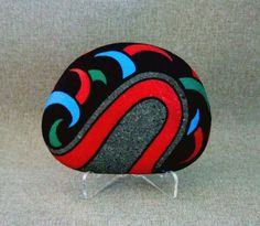 "The medium is acrylic paint and the Stone has been treated with an acrylic fixative to seal the stone. This Ishi is 4 "" by 5"" by 1 & 1/8"" (at the widest part). It comes with a clear, white acrylic easel that it can sit on. The red band is, is bordered with black. IshiGallery on Etsy. $450.00"
