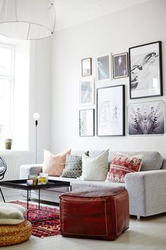 An all-white palette gets a '70s-inspired twist with the help of an ornate rug and pillows.   - HarpersBAZAAR.com