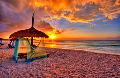 Not sure where this beach is... but it doesn't matter. There is a sunset & cabana. That's good enough for me!