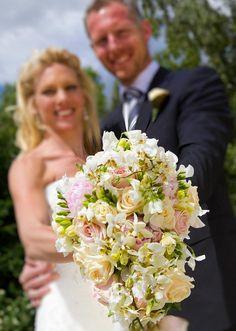 Brudebuketten i closeup, med brudeparret i baggrunden, sådan kan man også lave et bryllupsbillede.