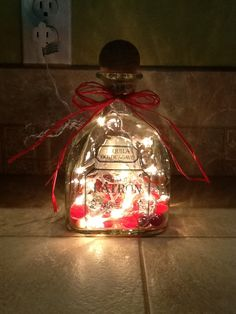 I am going to make this!  All you need are your choice color glass marbles in the bottom, LED light strand, and a ribbon!!      Patron Bottle Light