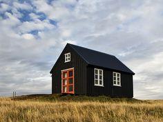 black cabin, white windows, orange door