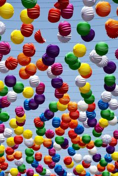 Rainbow of colors using round large ornaments floating around the blue skies