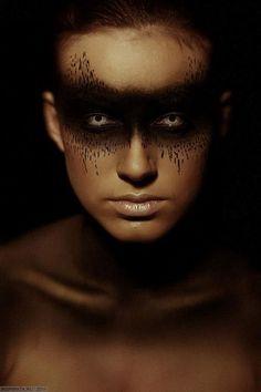 Dark mask style makeup.