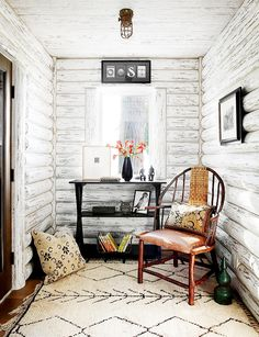 Reading nook in log cabin room with single desk