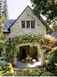 Stunning patio with beautiful greenery and stone arch. Love the manicured garden and stone floor.