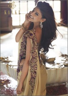 A stunning beige saree with purple corset blouse by Kalki