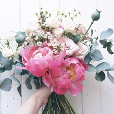 The perfect summer bridal bouquet with coral peonies, quicksand roses, jana spray roses, scabious pods, wax flower, poppy pods and silvery eucalyptus