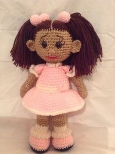 """Crochet doll with pink and white dress with pink bow embellishment and pink crochet hair """"ballies"""". Made with 100% acrylic yarn, fiberfill, and safety eyes. Made by Nanaknitsluv"""