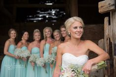 Old barn wedding photography of the bride and bridesmaids in soft pastel dresses and exquisite bouquets