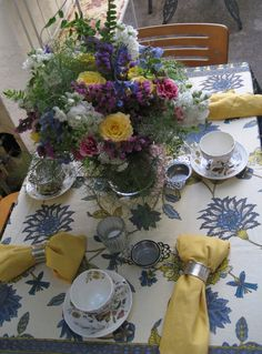 One of our afternoon teas. Small area, picturing one of two tables set up separately. Antique tea set, French-inspired table cloth, and a lil' flower arrangement I put together with Jon, June 2007.