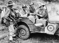 THE KOREAN WAR 1950 - 1953 Two fur-hatted Chinese sitting in the back of a jeep after being captured during an Australian assault. The Australian soldiers are Corporal K Hoare (left), Corporal C M Simmons (centre) and the driver is Private K J Fitzgerald.