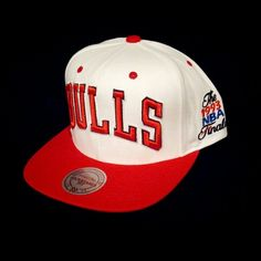 """Manufactured by Mitchell & Ness, this Hardwood Classics Flat Bill Chicago Bulls limited item features a red cloth flat bill with a white cap. This is a 1993 NBA Finals Edition Hat. The back features an adjustable snap strap. On the front you will find the name """"BULLS"""" embroidered in thick premium thread with the signature Mitchell & Ness logo embroidered in gold in the back. The side features the 93' NBA Finals logo embroidered in premium thread. IN STORE ONLY!"""