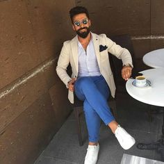 Wear a cream sportcoat and blue chinos if you're going for a neat, stylish look. Dress down this getup with white leather low top sneakers. Shop this look on Lookastic: https://lookastic.com/men/looks/blazer-long-sleeve-shirt-chinos/20600 — Beige Blazer — Black Pocket Square — White Long Sleeve Shirt — Blue Chinos — White Leather Low Top Sneakers