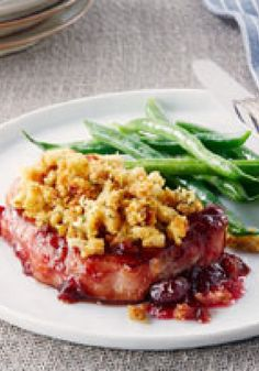Pork Chops with Cranberry Sauce & Stuffing — It only takes 10 minutes of prep time to pop these pork chops in the oven. They're baked on a layer of whole berry cranberry sauce with stuffing on top.