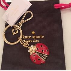 KateSpade LadyBug Key Fob New and Authentic gold toned Beautiful bejeweled bug has white sparkly stone eyes, shiny red wings,and smaller and larger black stone accents. Clips to use as bag jewelry. Comes with logo bag pouch. kate spade Accessories Key & Card Holders