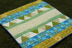"""A fun baby quilt like no other! Big bold bars of color run horizontally with two insets of coordinating green triangles to add a whole bunch of pizazz! It can be used as a baby quilt or simply as a small lap quilt.    The size on this blanket is 37"""" x 41"""". It is a nice size that a child can love for years. And the beautiful colors will brighten even the darkest winter day!"""