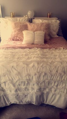 White and blush pink bedding, light gray walls, and gold accents.