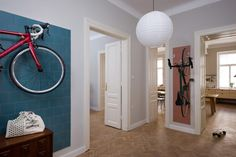 The kitchen and hallway walls of this apartment are painted in muted colours, with sections of blue and pink tiling marking out hooks for the owners to hang their bikes.