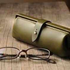 """ふと出会った古いドクターバッグに魅せられてつくった、""""Paka""""シリーズのメガネケース。口金の機能的なうつくしさと楽しさ、ふくらみのあるフォルム、しっとりとした革とつや消しの真鍮の質感、細部にまでこだわりを詰め込んだメガネケースです。       お気に入りのメガネに、こだわりのメガネケースはいかがでしょうか。       マチ幅を広めにとっておりますので、それほど大きくないメガネであれば2つ入れておくことができます。いつものメガネとおしゃれ用、パソコン用とリラックス用、老眼鏡とサングラス。   メガネを2つ持ち歩きたい方にもおすすめです。  また、内側には柔らかい革の仕切りをつけておりますので、メガネの間にはさんでおけば、メガネ同士がぶつかることもありません。       他のカラーもご用意しておりますので、出品されていないカラーをご注文頂く場合は、注文後にご希望のカラーをご連絡ください。 カラーバリエーションはオレンジ、コニャック、オリーブ、チョコ、アオの5色です。      …"""