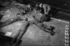 """On June 6, 1944, """"D-Day,"""" Allied troops stormed the beaches of Normandy, France. Magnum founder Robert Capa accompanied the first wave of troops and documented this pivotal day in history. DORSET, WEYMOUTH, England—Onboard the anchored U.S. Coast Guard transport ship Samuel Chase. Planning the D-Day landings, using a model of Omaha Beach, June 1-5, 1944."""