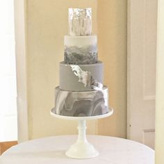 Winter themed silver and grey wedding cake with marble effect fondant, hand painting and silver leaf by Blossom & Crumb.
