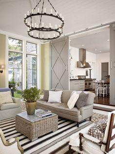 """A Williams-Sonoma striped rug set on pavers neutralizes walls painted Farrow & Ball's """"Cooking Apple Green."""" A Circa Lighting sconce and Paul Ferrante chandelier create tension with their opposing scales. The club chair is covered in Rose Tarlow fabric."""
