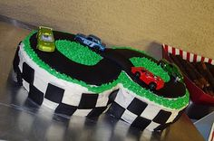 "Race car cake via thecreativepaige.  It's two round 8"" cakes pushed together with black fondant for the racing track.  The blogger said she found this cake via punchbowl dot com."