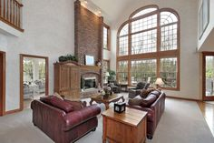 Here's another living room with an immense, arched full height window wall. Brick fireplace stretches to the ceiling, standing over a pair of red leather sofas, natural wood tables, and patterned easy chairs in the distance.