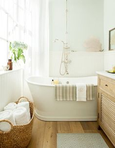 Lovely bath with vintage cast iron tub, Perrin & Rowe fixtures, pale green paint color + reclaimed white oak floors.