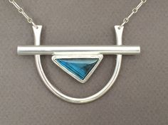 This one-of-a-kind handmade necklace features a large triangular labradorite gemstone which is bezel set and appears to be suspended from the