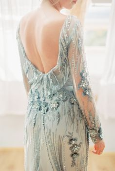 A silver wedding dress with beaded floral details and open back.