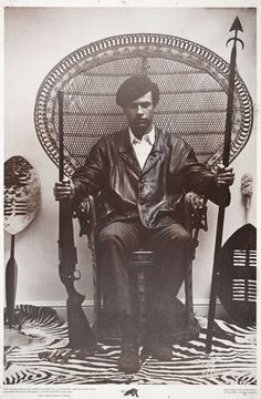 This poster of Huey P. Newton was made from a photo taken by Eldridge Cleaver in 1967 at civil rights attorney Beverly Axelrod's house. Eldridge made the original posters and then gave them to the Black Panther Party to sell. It quickly became the leading poster of its time and was sold throughout the world. The poster is a symbol of man's evolution in self-defense, from the spear and shield to the shotgun.
