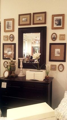 This might work in the dining room or bedroom.  I like the collection of old photos -- especially the small oval ones -- around the mirror.  Perhaps this arrangement of mirror and old photos would work in the upstairs hall, too.