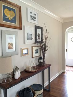 Benjamin Moore Pale Oak fIn a hallway with medium toned wood floors and a small art gallery.