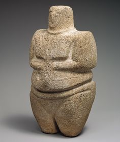 3000-2000 BCE. Standing female figure,10 5/8 in., wearing a strap and a necklace,  This shows the beginning of a long sculptural tradition in bronze age S.W. Arabia of extreme simplification and strict rectangular shape. Sandstone, quartzite.