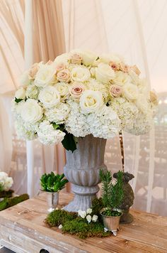 An urn is filled with muted roses and hydrangeas for a rustic feel. #weddingdecor #weddingflowers