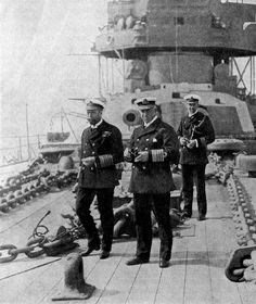 """King George V (left) and Admiral Callaghan onboard British battleship HMS Neptune. In the background is """"A"""" turret with 2 12-inch Mk XI guns."""