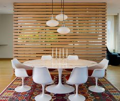 This wooden slat wall partitions off the dining area and gives it a nice backdrop, as well as hiding the stairs behind it.