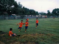 cheerful elementary school children playing soccer in Indonesia, without loading them laugh.