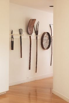 A collection of vintage farm tools hangs in the hallway